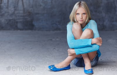 Cute blond girl in azure clotning.