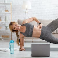 Fitness lessons online at home. Woman in sportswear makes side plank on mat on floor with laptop