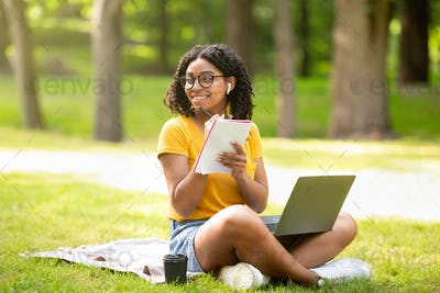 Online education. Happy black girl taking notes while watching web lesson on laptop at park