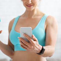Good news in smartphone. Muscular woman with bottle of water looks at phone