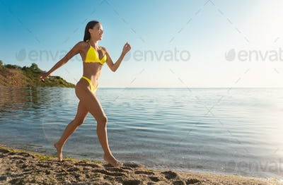 Happy Girl On Beach Running In Bikini Near Sea Outdoor