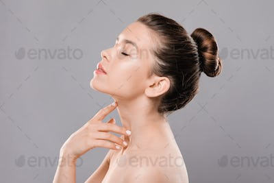 Sexual lady with closed eyes touching her neck