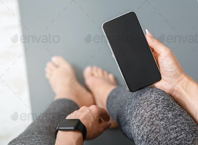 Devices for sport. Woman with smart watch and phone in her hand with blank screen, sits on mat
