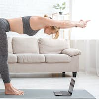 Fitness online at home during epidemic. Woman makes tilt, standing on mat with laptop