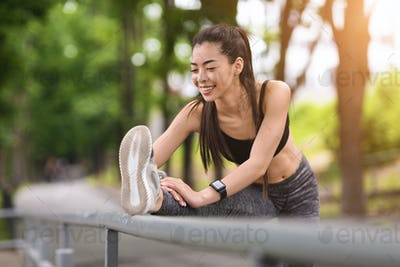 Flexible Asian Girl Stretching Leg Muscles While Working Out In City Park