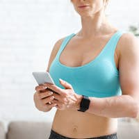 Fitness trainer remotely at home. Muscular woman with smart watch looks at phone