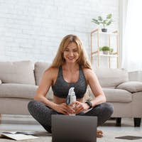 Online coach has online chat after training with followers. Woman sits on floor, look at laptop