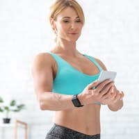 Online training. Woman with smart watch checks smartphone in living room