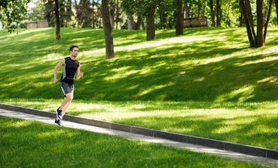 Guy in sportswear jogging at track, on lawn in park