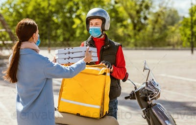Courier Giving Pizza Boxes To Woman Wearing Mask Standing Outside