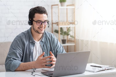 Conversation with client and video call. Guy with glasses and headset gesticulating with hands and