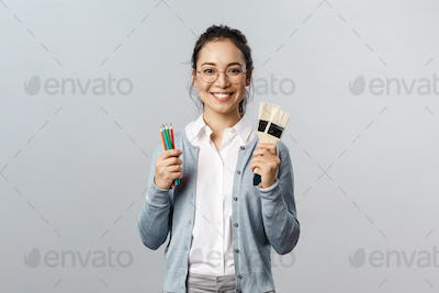 Hobbies, creativity and art concept. Cheerful young asian woman in glasses spend leisure with fun