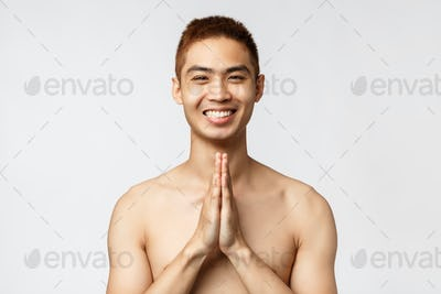 Beauty, people and home concept. Portrait of peaceful, relaxed asian man smiling happy, show namaste