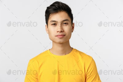 Close-up studio shot asian charming, modern hipster man in yellow t-shirt, smiling with confident
