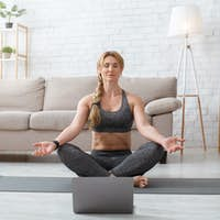 Online trainer practicing yoga. Woman in lotus pose with closed eyes, meditation on mat on floor