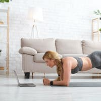 Middle aged woman in sportswear with fitness tracker makes plank and raise leg on floor with laptop