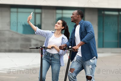 Couple having ride on motorized kick scooters, taking selfies