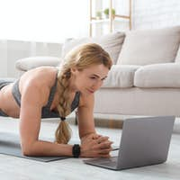 Middle aged woman in sportswear with fitness tracker makes plank at mat on floor and looks at laptop