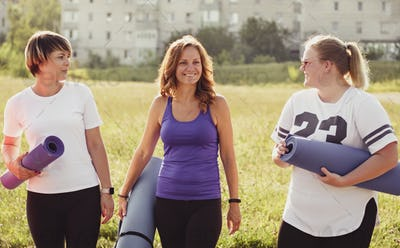 Three happy young women carrying yoga mats