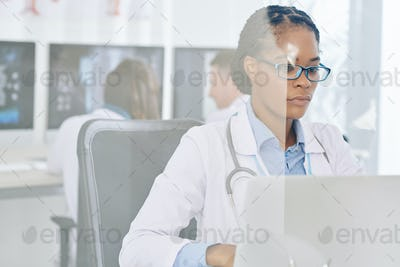 Serious doctor working on laptop