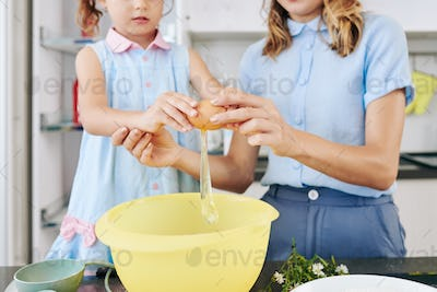 Mother and daughter cracking egg