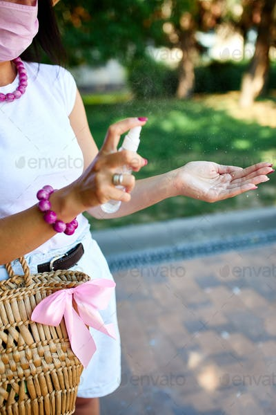 Hand of trendy woman in with straw bag, using hand sanitizer gel in city street