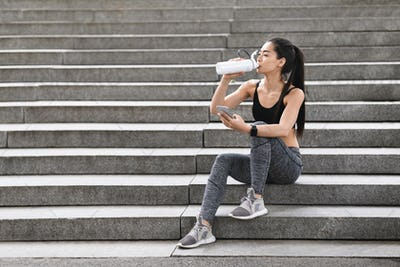 Sporty Asian Girl Drinking Water And Using Smartphone, Resting After Training Outdoors