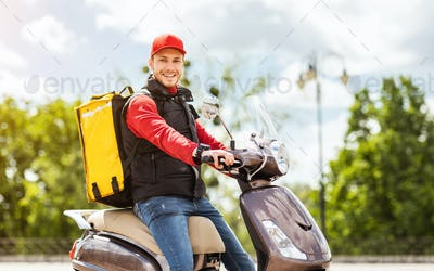 Courier Man With Yellow Backpack Sitting On Scooter Smiling Outside
