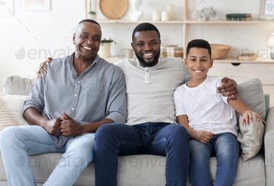 Portrait of happy black multigenerational men family posing on couch at home