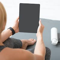 Fitness lessons at home. Woman with tablet with blank screen sits on mat with bottle