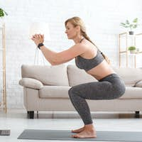 Woman with fitness tracker crouches and watches at laptop in living room interior