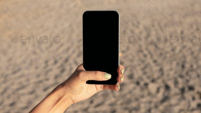 Female Hand Holding Mobile Phone With Blank Screen Against Sand