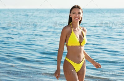 Girl In Yellow Bikini Posing At Seaside Smiling To Camera