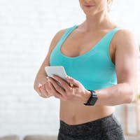 Online trainer tips. Adult woman in sportswear with fitness tracker typing on smartphone