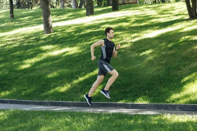 Muscular man in sportswear runs along track in green park