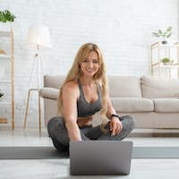 Smiling woman in sportswear looks at laptop, sitting on floor on sports mat in living room interior
