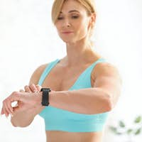 Exercises and biological rhythms. Attractive woman in sportswear checks fitness tracker in living