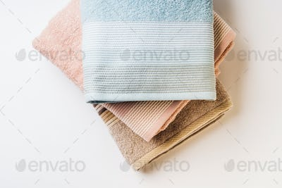 Pastel color clean folded towels on white background