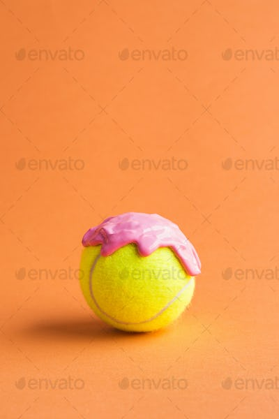 Tennis ball with pink paint on orange
