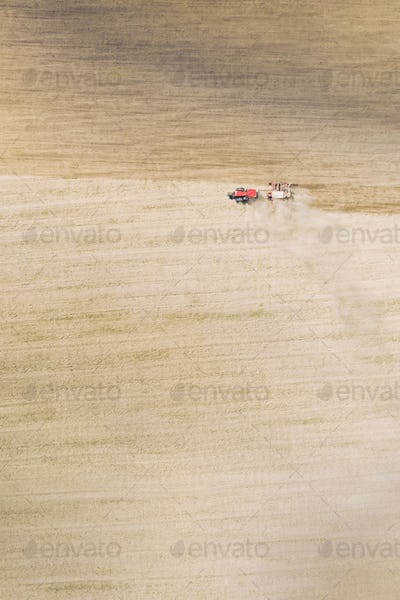 Aerial View. Tractor With Seed Drill Machine Sowing The Seeds For Crops In Spring Season. Beginning