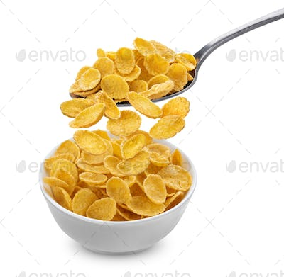 Corn flakes falling from spoon into bowl isolated on white background