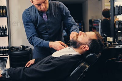 Stylish barber grooming a man's beard in a saloon.