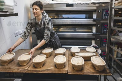 A baker in an artisan bakery making sourdough bread.