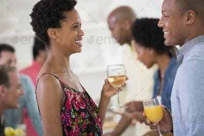 A networking office party or informal event. A man and woman, with a crowd around them.