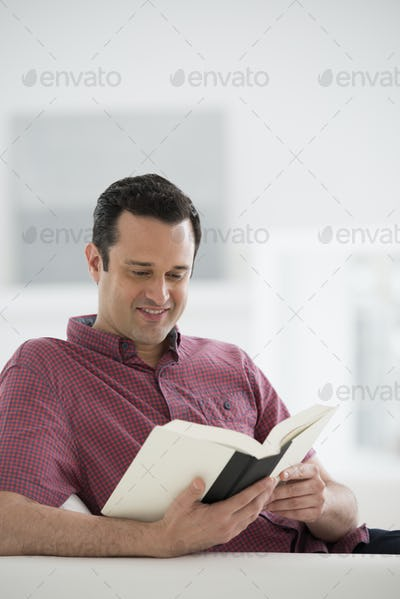 A bright white room interior. A man sitting reading a book.