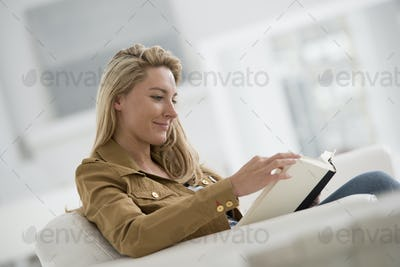 A bright white room interior. A woman sitting reading a book.