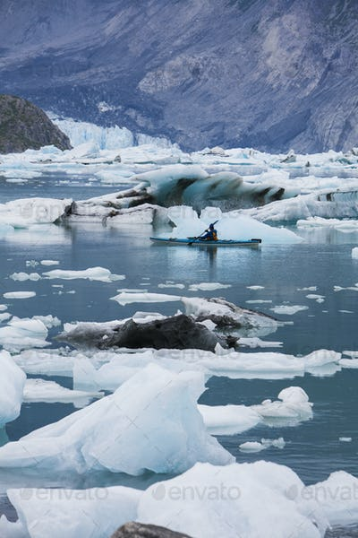 A sea kayaker paddling through ice in the lagoon at the terminus of the McBride Glacier.