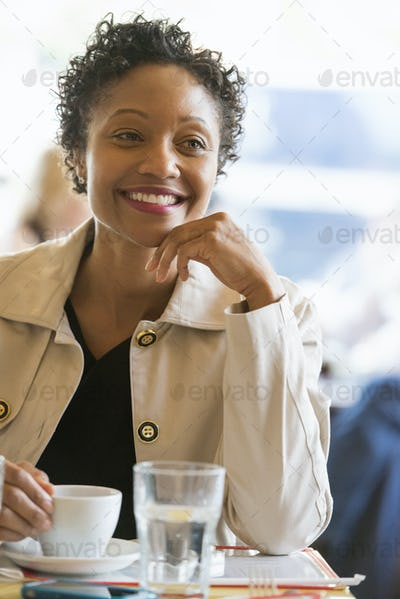 City life. A woman wearing a beige jacket sitting at a table in a cafe