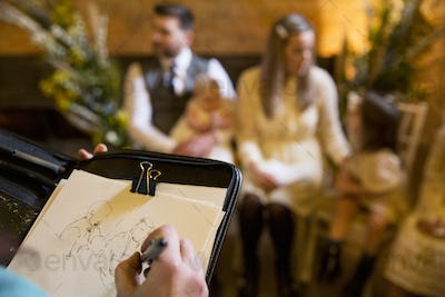 Over the shoulder view of artist sketching family during naming ceremony in an historic barn.