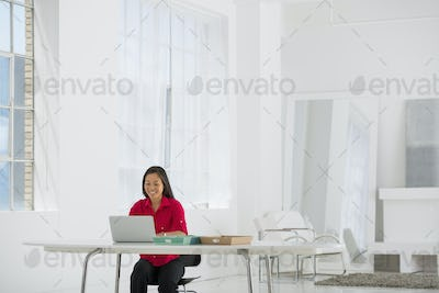 An office in the city. Light and airy working environment. A woman seated using a laptop.
